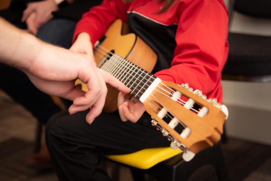 Kinde lernt das Gitarrenspiel