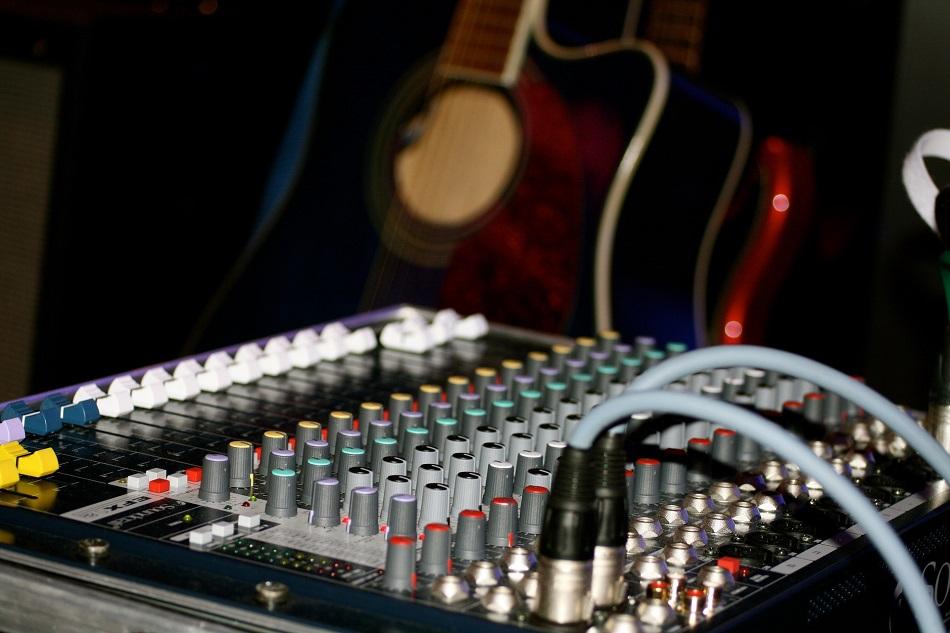 Studiomusiker*in mit Gitarre und Mischpult